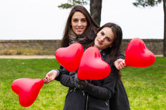 Two smiling girls holding hearts Royalty Free Stock Photography