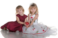 Two smiling girls holding a red apple Royalty Free Stock Images