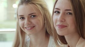 Two smiling girls look in the camera. Two smiling beautiful girls look in the camera in shopping center stock video