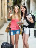 Two smiling girls with map. Chasing city streets and looking for hotel stock image