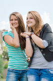 Two smiling girls over blue skype outdoors Royalty Free Stock Images
