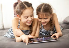 Two smiling girls pointing at touchscreen of tablet Stock Image
