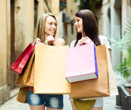 Two smiling girls rejoicing purchases Royalty Free Stock Photo