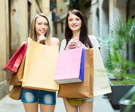 Two smiling girls rejoicing purchases Royalty Free Stock Photography