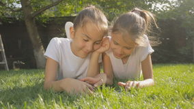 Two smiling girls relaxing on grass and playing on digital tablet. Two girls relaxing on grass and playing on digital tablet stock footage