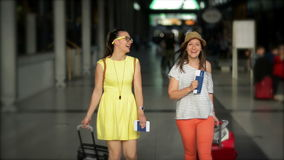 Two smiling girls are rolling large travel bags at the airport. Pretty woman in yellow dress and eyeglasses is traveling. With Her Female Friend Wearing Striped stock footage
