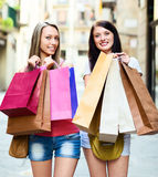 Two smiling girls with shopping bags walking Royalty Free Stock Image