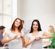 Two smiling girls showing heart with hands Stock Images