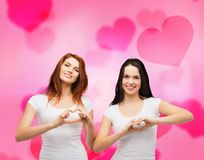 Two smiling girls showing heart with hands Stock Photos