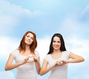 Two smiling girls showing heart with hands Royalty Free Stock Images