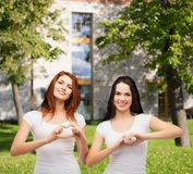 Two smiling girls showing heart with hands Royalty Free Stock Image