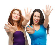 Two smiling girls showing their palms Royalty Free Stock Photos