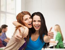 Two smiling girls showing thumbs up stock images