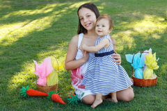 Two smiling girls sisters baby and teen with chocolate eggs for Stock Photos