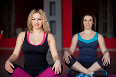 Two smiling girls sit cross-legged in fitness center. Two smiling pretty girls sit cross-legged in lotus pose in sports hall Royalty Free Stock Images