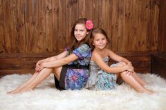Two smiling girls sit  on white fur Stock Photography