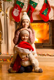 Two smiling girls sitting next to fireplace at Christmas eve Stock Image