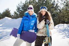 Two smiling girls with snowboards. Two beautiful smiling girls with snowboards standing outside, sunny winter day Stock Photos