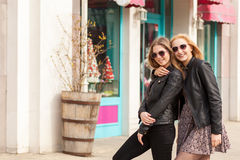 Two smiling girls in sunglasses embracing and looking at camera Royalty Free Stock Image