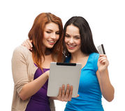 Two smiling girls with tablet pc and credit card Stock Image