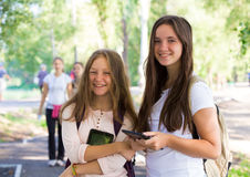 Two smiling girls with the tablets Royalty Free Stock Images