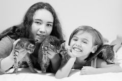 Two smiling girls and three cute tabby kittens. Close up of two cute girls lying on their stomachs and holding three cute little tabby kittens.  Girls are about Royalty Free Stock Photo