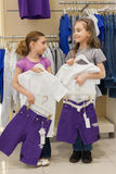 Two smiling girls trying on the same dress in the store Royalty Free Stock Photography
