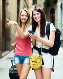 Two smiling girls using  smartphone  for find a way Royalty Free Stock Photos