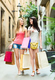Two smiling girls walking and discussing purchases Stock Photos