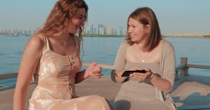 Two smiling girls in light dressesg are watching photos on smartphone. Blue water lake and cityscape on the background. Two smiling girls are watching photos on stock video