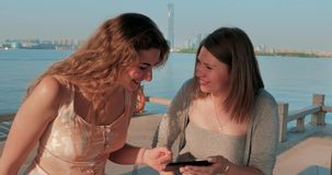 Two smiling girls in light dressesg are watching photos on smartphone. Blue water lake and cityscape on the background. Two smiling girls are watching photos on stock footage