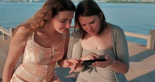 Two smiling girls in light dressesg are watching photos on smartphone. Blue water lake and cityscape on the background. Two smiling girls are watching photos on stock video footage