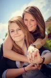 Two smiling girls whispering gossip Royalty Free Stock Photos