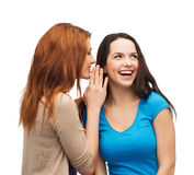 Two smiling girls whispering gossip Royalty Free Stock Photos