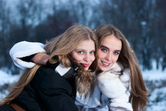 Two smiling girls in the winter forest stock photo