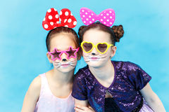 Two smiling glamour girls in funny sunglasses on blue background Royalty Free Stock Images