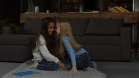 Two smiling grade school girls telling secrets. Lovely mixed race school girl whispering secret to her amazed friend and laughing while sitting on the floor in stock footage