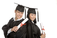 Two smiling graduates at the white background Royalty Free Stock Photography
