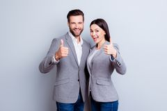 Two smiling happy businesspeople in formalwear showing thumbs-up on gray background stock photo