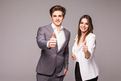 Two smiling happy business people in formalwear showing thumbs-up on gray background. Two smiling happy businesspeople in formalwear showing thumbs-up on gray Royalty Free Stock Photos
