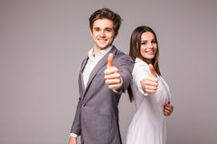 Two smiling happy business people in formalwear showing thumbs-up on gray background. Two smiling happy businesspeople in formalwear showing thumbs-up on gray Royalty Free Stock Images