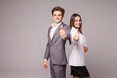 Two smiling happy business people in formalwear showing thumbs-up on gray background. Two smiling happy businesspeople in formalwear showing thumbs-up on gray Royalty Free Stock Photo