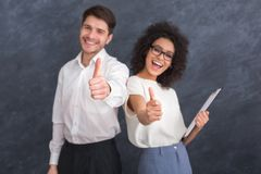 Two smiling happy businesspeople in formalwear showing thumbs-up royalty free stock photography