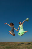 Two smiling and happy girls jumping Royalty Free Stock Image