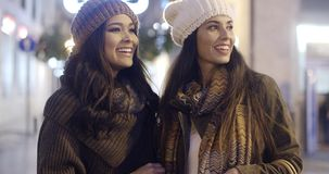 Two smiling happy women in winter outfits. Two smiling happy attractive young women friends in winter outfits standing outdoors in an urban street at night stock video