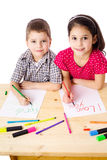 Two smiling kids draw for mum. Two smiling kids at the table draw with crayons for mum, isolated on white Stock Images