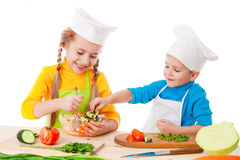 Two smiling kids mixing salad Stock Photography