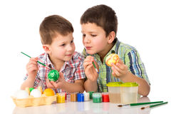 Two smiling kids painting easter eggs together at the table Stock Photo