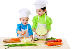 Two smiling kids preparing salad Stock Photography
