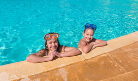 Two smiling kids relaxing together on swimming pool stock photo